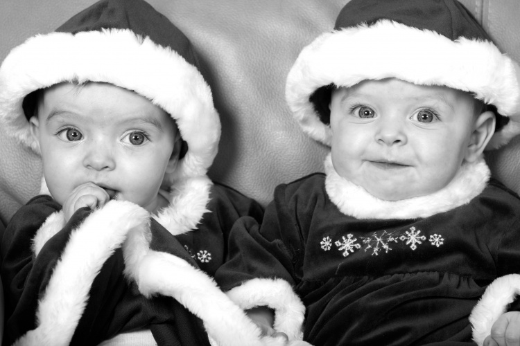 Twins wearing santa hats by Sharif Mohammadi